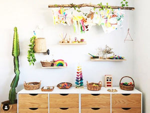 A colourful scene showing a childs bedroom with a timber cabinet, wooden toys and a trio of shelves sits above, holding more wooden toys, baskets and sensory play objects.