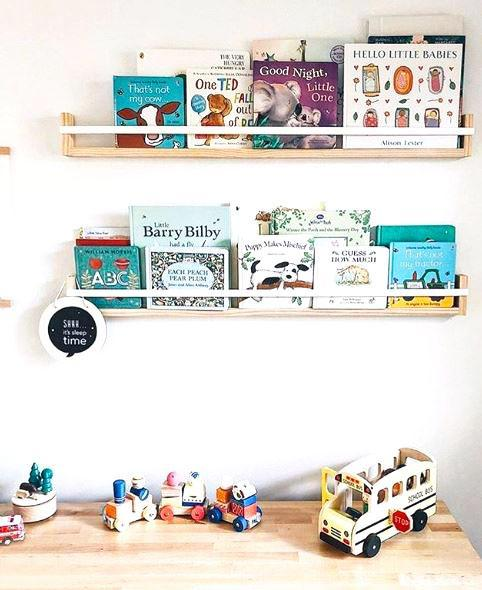 2 timber book shelves on a white wall, filled with children's books. They sit above a timber cabinet with wooden toys displayed