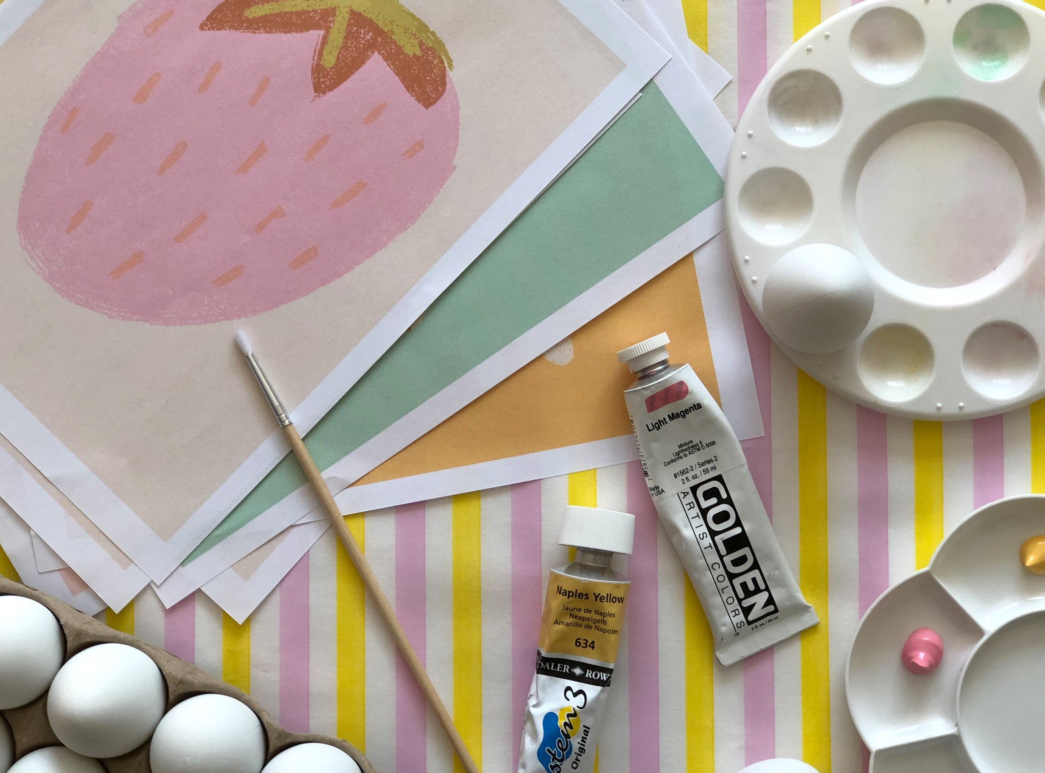 Easter Egg craft equipment including paint, paintbrushes and paint mixing palette