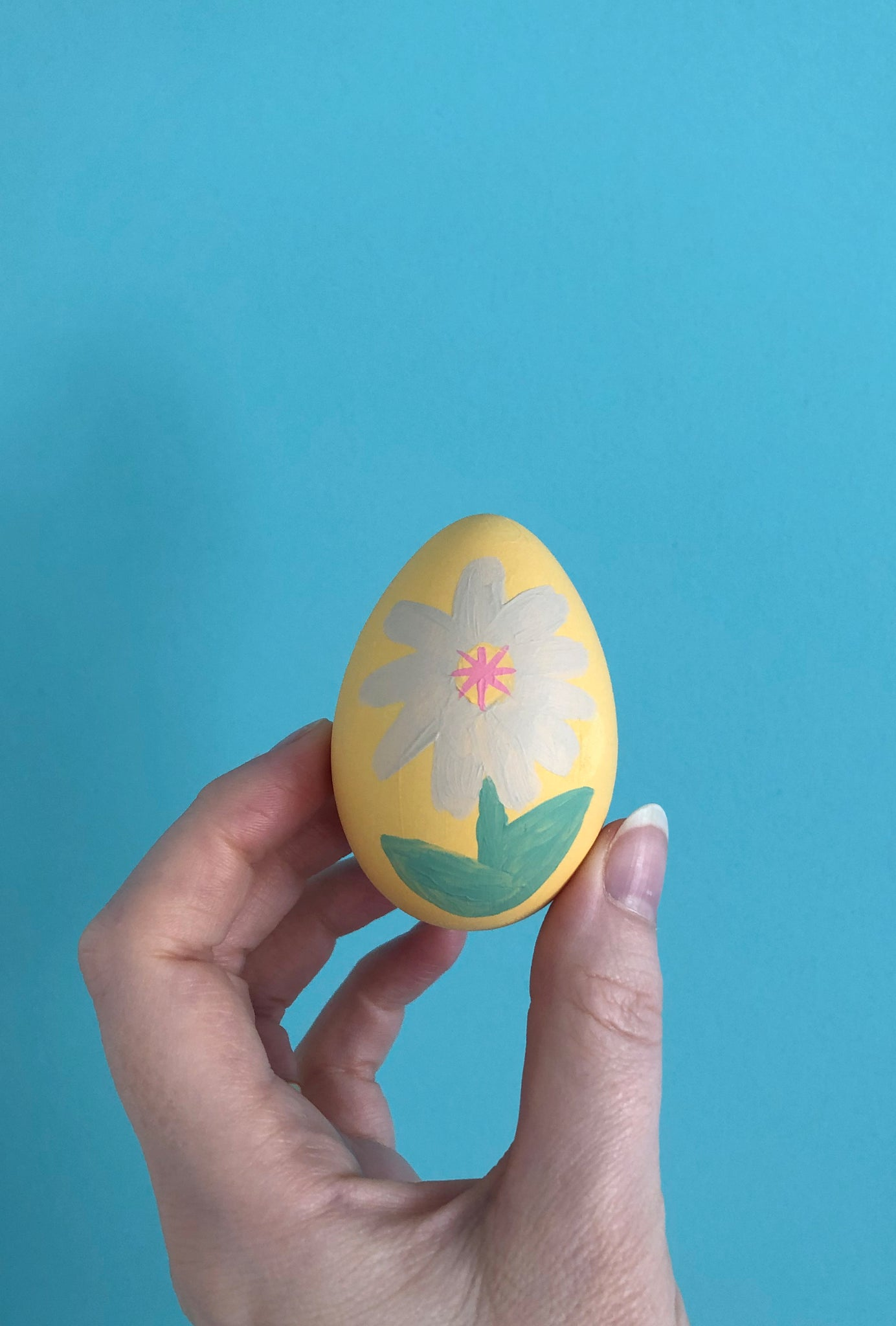 Finished painted daisy on Easter egg crafts for kids with blue background