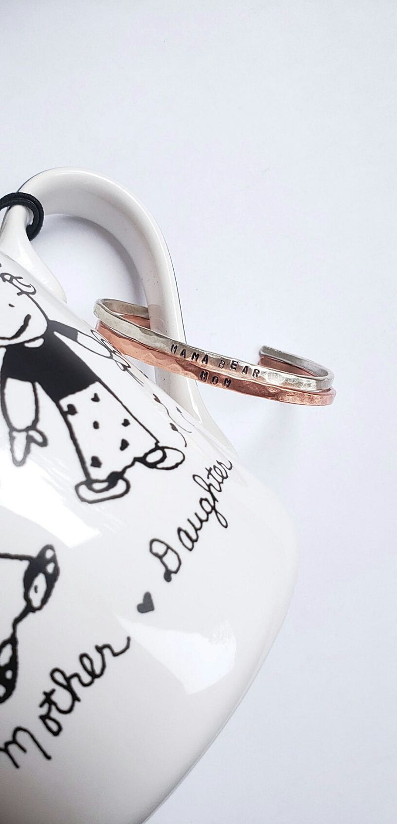 "2 bracelets hanging from a Mother's Day mug. 1 argentium sterling silver bracelet which says ""mama bear"" and 1 copper bracelet says ""mom"""