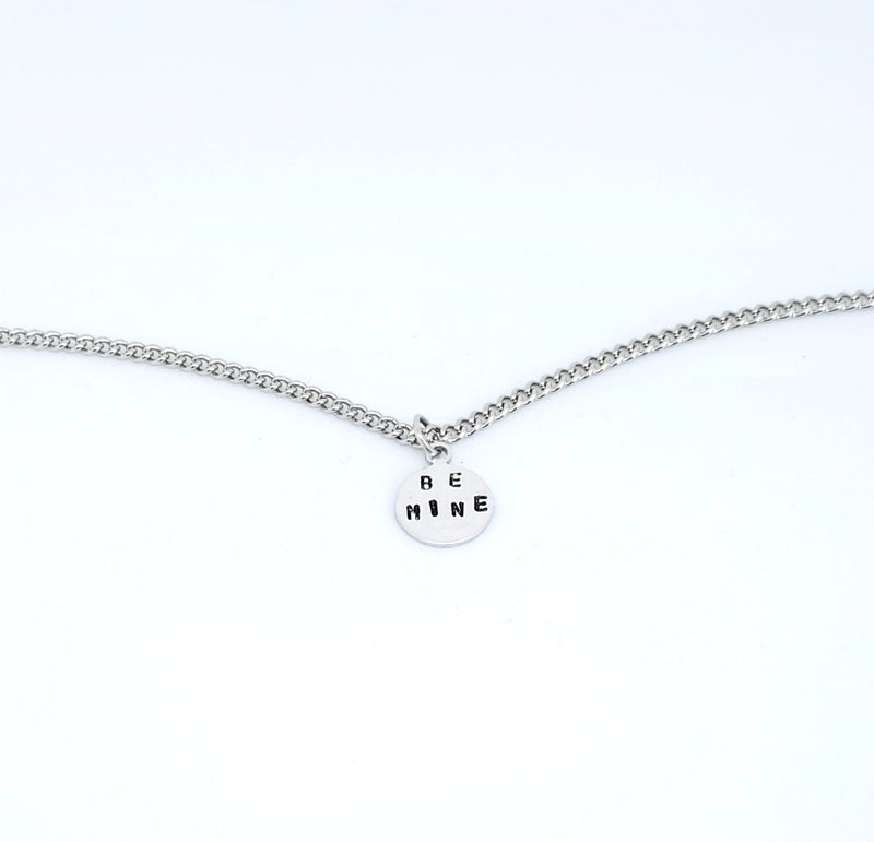 A handmade necklace with stamped words 'Be Mine'