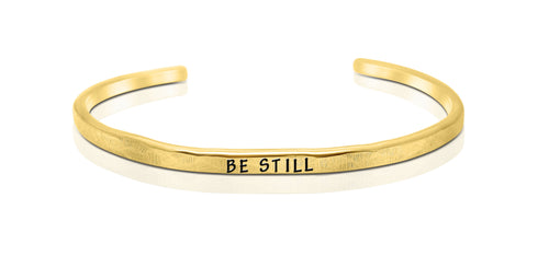 "A handmade and handstamped GOLD COLOURED bracelet with the word ""be still"" written on it waiting to be bought"
