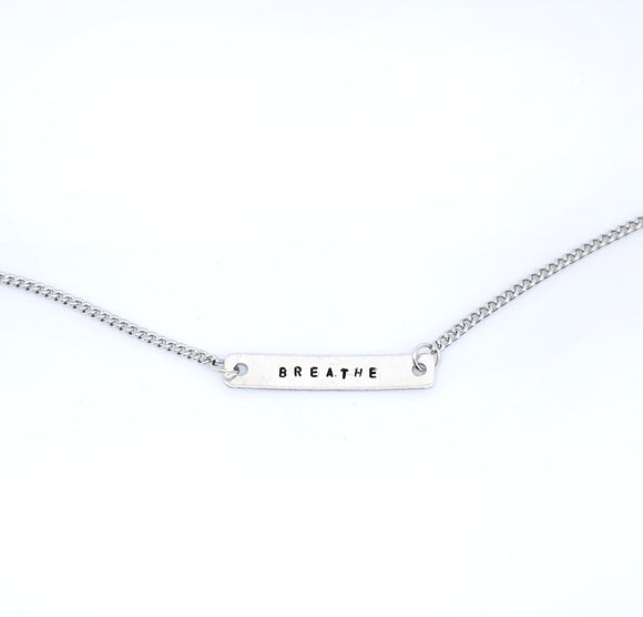 A handmade necklace with stamped words 'Breathe'