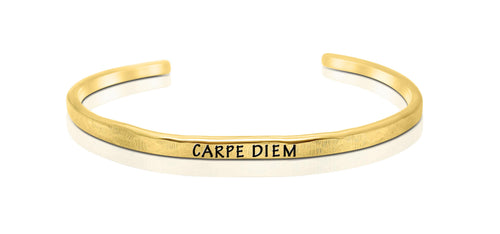 "A handmade and handstamped GOLD COLOURED bracelet with the word ""carpe diem"" written on it waiting to be bought"