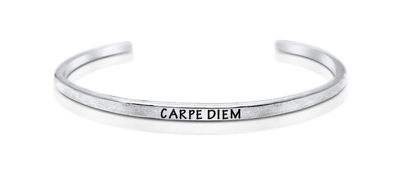 "A handmade and handstamped ARGENTIUM STERLING SILVER bracelet with ""carpe diem"" written on it waiting to be bought"