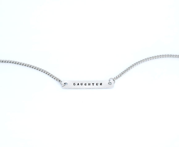 A handmade necklace with stamped word 'Daughter'