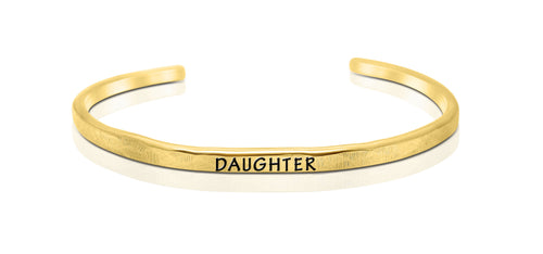 "A handmade and handstamped GOLD COLOURED bracelet with the word ""daughter"" written on it waiting to be bought"