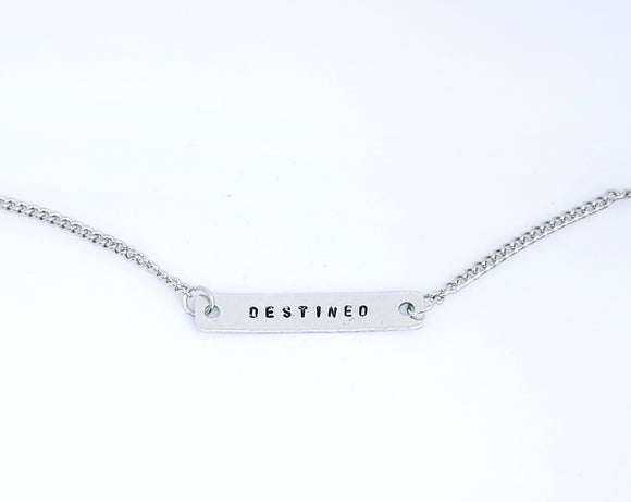 A handmade necklace with stamped word 'Destined'