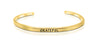 "A handmade and handstamped GOLD COLOURED bracelet with the word ""grateful"" written on it waiting to be bought"