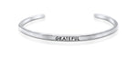 "A handmade and handstamped ARGENTIUM STERLING SILVER bracelet with ""grateful"" written on it waiting to be bought"
