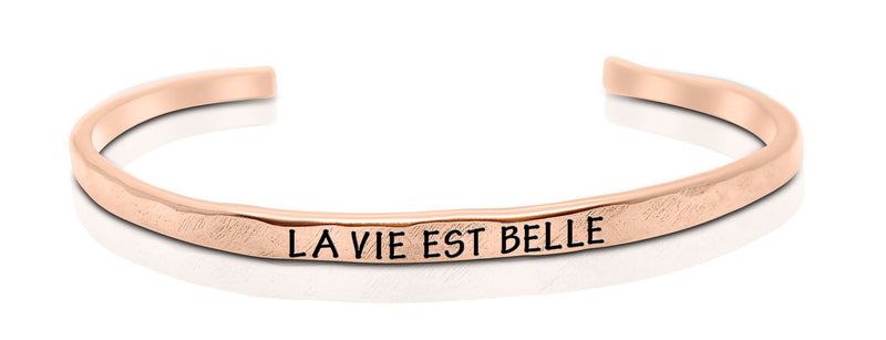 "A handmade and handstamped COPPER bracelet that has the word ""la vie est belle"" written on it waiting to be bought"
