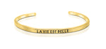 "A handmade and handstamped GOLD COLOURED bracelet with the word ""la vie est belle"" written on it waiting to be bought"