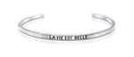 "A handmade and handstamped ARGENTIUM STERLING SILVER bracelet with ""la vie est belle"" written on it waiting to be bought"