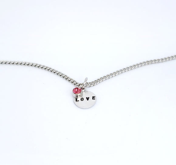 A handmade necklace with stamped word 'Love' + pink Gem