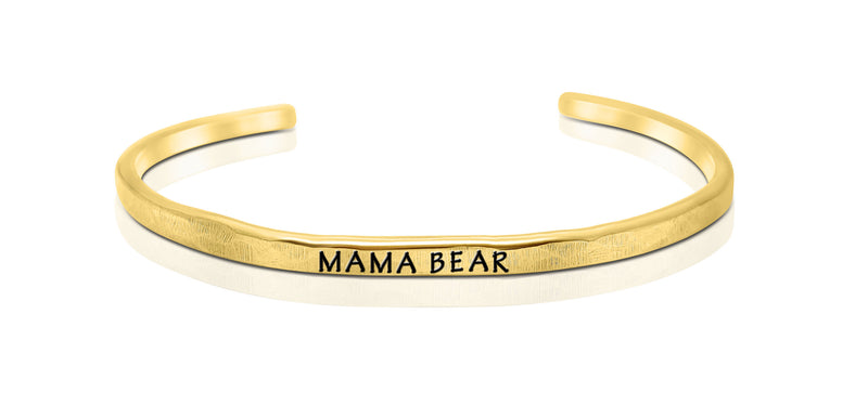 "A handmade and handstamped GOLD COLOURED bracelet with the word ""mama bear"" written on it waiting to be bought"