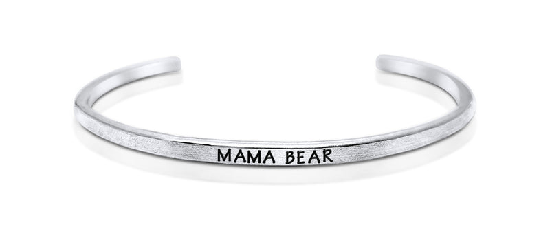 "A handmade and handstamped ARGENTIUM STERLING SILVER bracelet with ""mama bear"" written on it waiting to be bought"