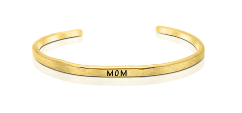 "A handmade and handstamped GOLD COLOURED bracelet with the word ""mom"" written on it waiting to be bought"
