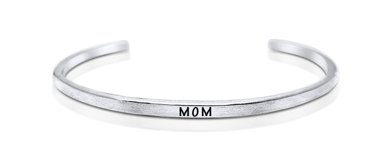 "A handmade and handstamped ARGENTIUM STERLING SILVER bracelet with ""mom"" written on it waiting to be bought"