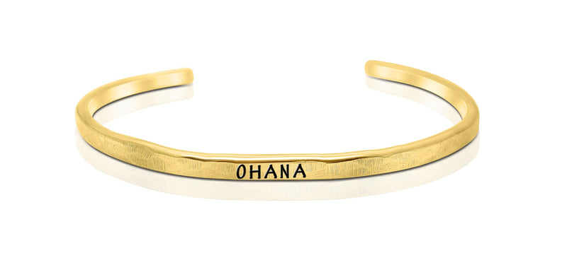"A handmade and handstamped GOLD COLOURED bracelet with the word ""ohana"" written on it waiting to be bought"