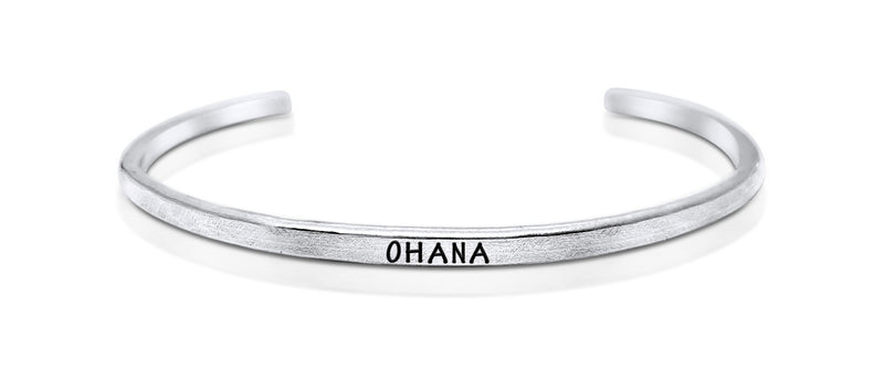"A handmade and handstamped ARGENTIUM STERLING SILVER bracelet with ""ohana"" written on it waiting to be bought"