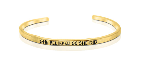 "A handmade and handstamped GOLD COLOURED bracelet with the word ""she believed, so she did"" written on it waiting to be bought"