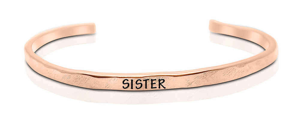 "A handmade and handstamped COPPER bracelet that has the word ""sister"" written on it waiting to be bought"