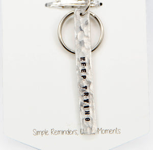 A handmade key chain with stamped words 'Keep Trying'