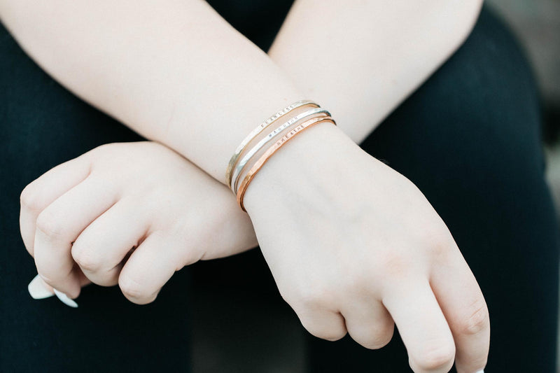 A caucasian woman's arms wearing 1 brass bracelet saying fearless, 1 silver bracelet saying warrior, 1 copper bracelet saying breathe