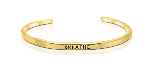 "A handmade and handstamped GOLD COLOURED bracelet with the word ""breathe"" written on it waiting to be bought"