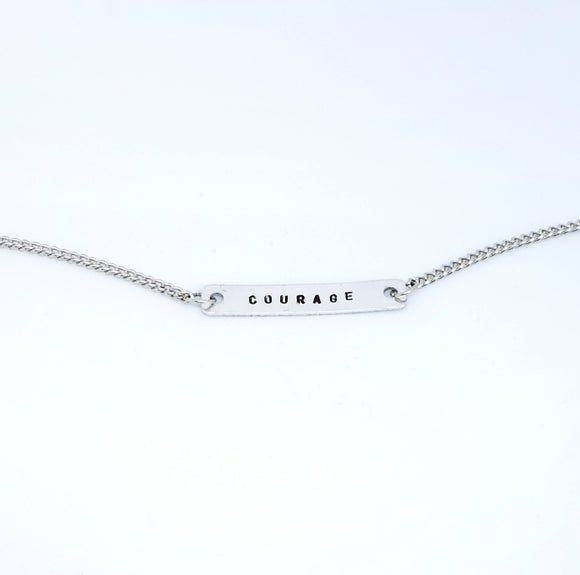 A handmade necklace with stamped words 'Courage'