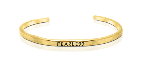 "A handmade and handstamped GOLD COLOURED bracelet with the word ""fearless"" written on it waiting to be bought"