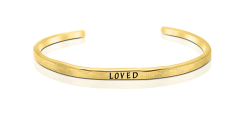 "A handmade and handstamped GOLD COLOURED bracelet with the word ""loved"" written on it waiting to be bought"
