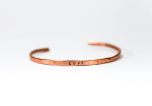 A handmade COPPER bracelet with stamped word 'love'