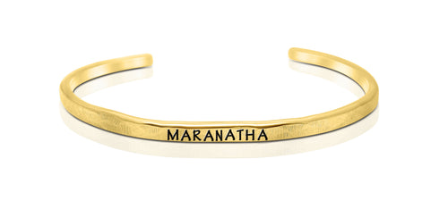 "A handmade and handstamped GOLD COLOURED bracelet with the word ""maranatha"" written on it waiting to be bought"