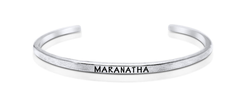"A handmade and handstamped ARGENTIUM STERLING SILVER bracelet with ""maranatha"" written on it waiting to be bought"