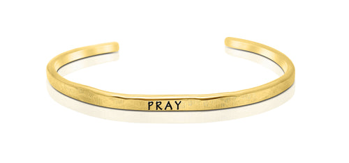 "A handmade and handstamped GOLD COLOURED bracelet with the word ""pray"" written on it waiting to be bought"