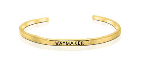 "A handmade and handstamped GOLD COLOURED bracelet with the word ""waymaker"" written on it waiting to be bought"