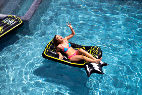 RIOT Energy custom pool floatie. Girl laying in the water on the floatie smiling and giving a peace sign.