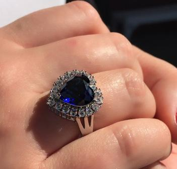 BLUE CRYSTAL HEART RING SURROUNDED IN A SPARKLING CUBIC ZIRCONIUM SETTING