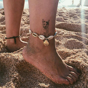 Shell Beads Anklet Worn On Beach With A Cat Tattoo