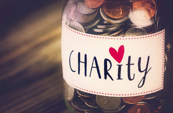 """Jar with coins it it and a label that says """"charity"""""""