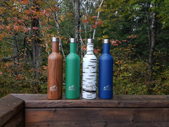Woodland, Forest, Birch, and Navy Wellington Bottles lined up on a wooden railing.