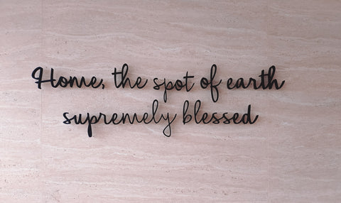 Home, the spot of earth supremely blessed, written in cursive on a wooden background.
