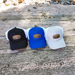 Chilly Moose Midnight, Lake and Granite Adventure Caps lined up in a row outdoor on a large rock