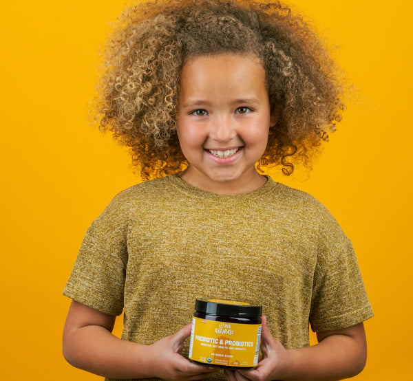 Child holding probiotics for kids container