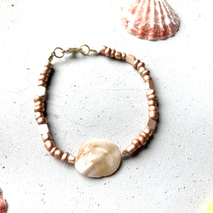 front top shot of mermaid inspired bracelet with seashells in the background. bracelet has mother of pearl seashell focal bead with rose gold metallic seed beads and a gold lobster clasp.