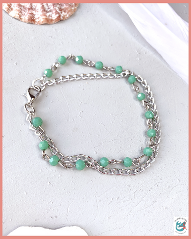 image of turquoise and silver dainty chain bracelet on a grey desk with seashells and feathers. the bracelet is one of a kind and handmade using upcycled materials. vintage boho western bracelet is only available at www.annamollysbychelsea.com
