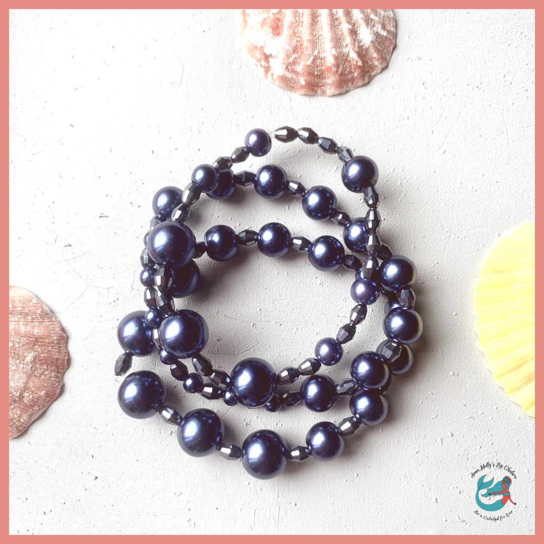 flat lay of bracelet set and seashells. bracelet set includes three elastic bracelets with navy blue pearls and faceted glass beads