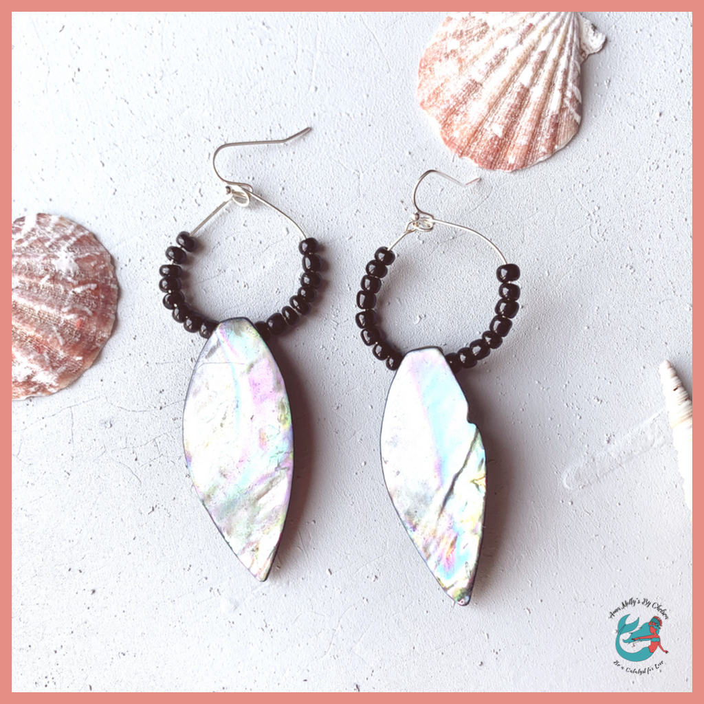 drop hoop dangle earrings featuring a pretty iridescent shell. hoop is made of recycled silver ear wire and is beaded with fair trade certified black seed beads. earrings are sitting on a grey desk with seashells in the background.